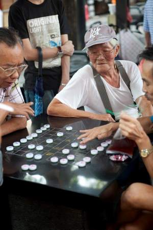 Men playing xiangqi, or Chinese chess, in Singapore
