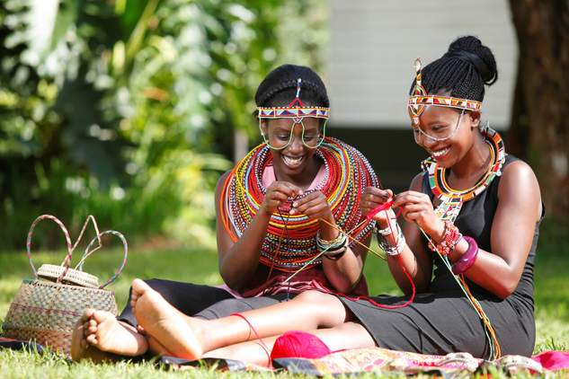 Adolescent girls talking and crafting together in Kenya