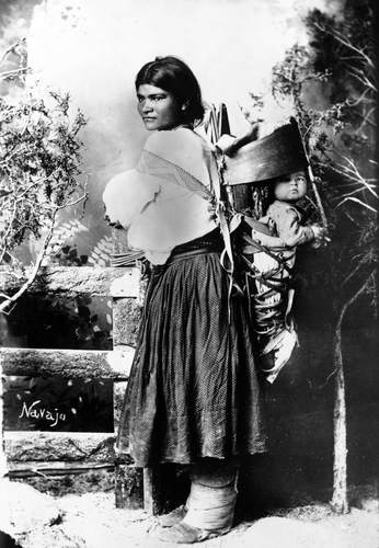 Navajo woman carrying child in a cradleboard. Cradleboards may be carried on the mother's body as shown in this photo, but they may also be hung up in a tree or in the wall of a house.