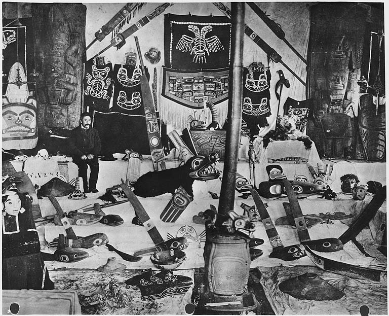 Tlingit Chief Charles Jones Shakes, pictured at home in Wrangell, Alaska, with an array of his possessions, ca. 1907. The Tlingit, a culture dependent on fishing, exemplify the hierarchical structure of complex hunter-gatherer societies