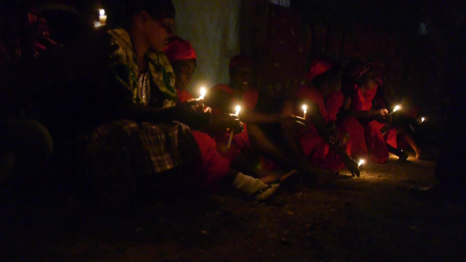 Women in red dresses are dimly lit by candles in their hand while seated on the earth floor of a temple in Haiti.