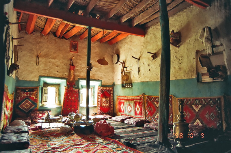 Interior of a plaster sided home, with sticks protruding from walls where objects are let to hang. Brightly painted walls and roof beams, with pillows and carpets covering the floor.