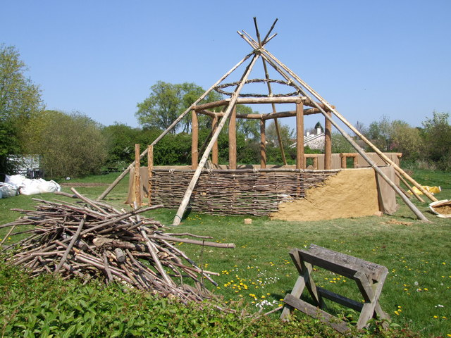 Image of a partially constructed roundhouse replica in the UK, one side is partially finished with mud covering the stick and stone exterior.