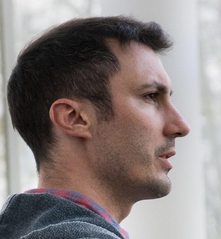 A profile photo of Damian Blasi wearing a sweatshirt and a scarf.