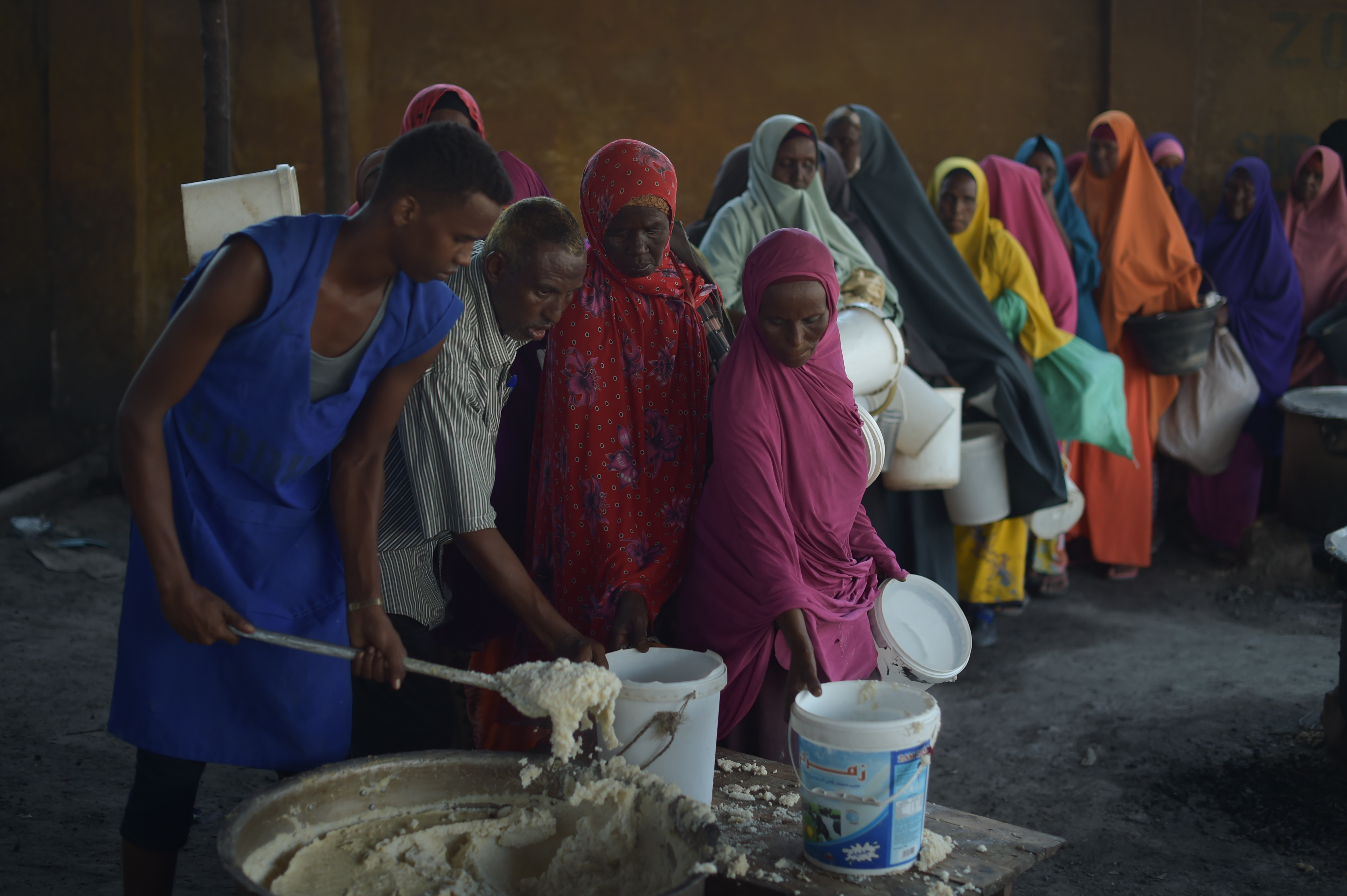 Women line up to gather cooked food from a large pot.