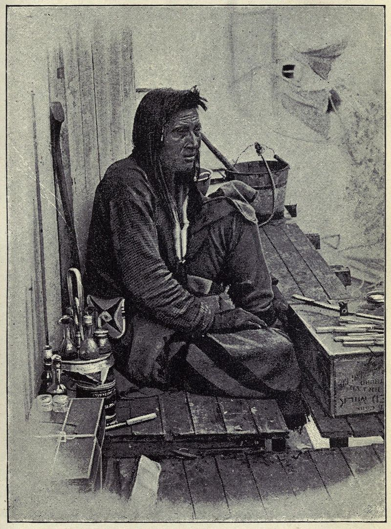 A man sits, surrounded by tobacco, looking off into the distance.