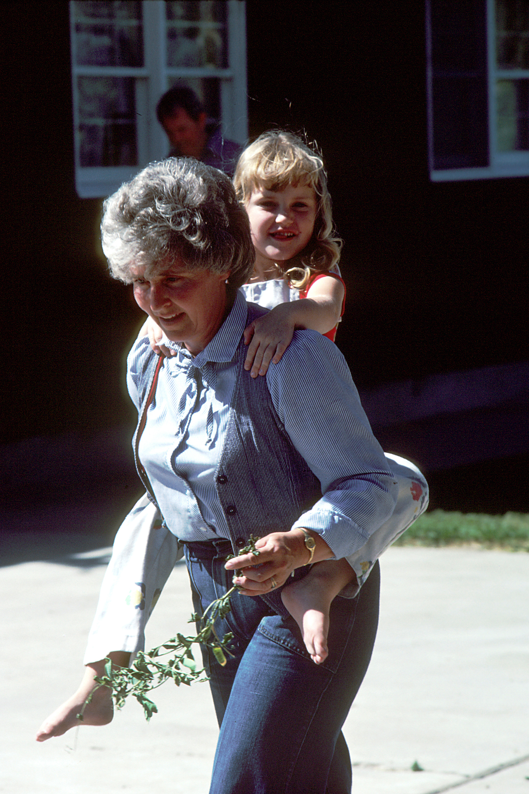 A grandmother carries her granddaughter on her back while holding herbs.