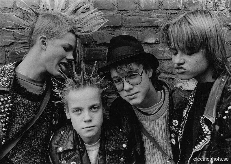 A group of four boys with mowhawks and silly expressions pose together against a brick wall.