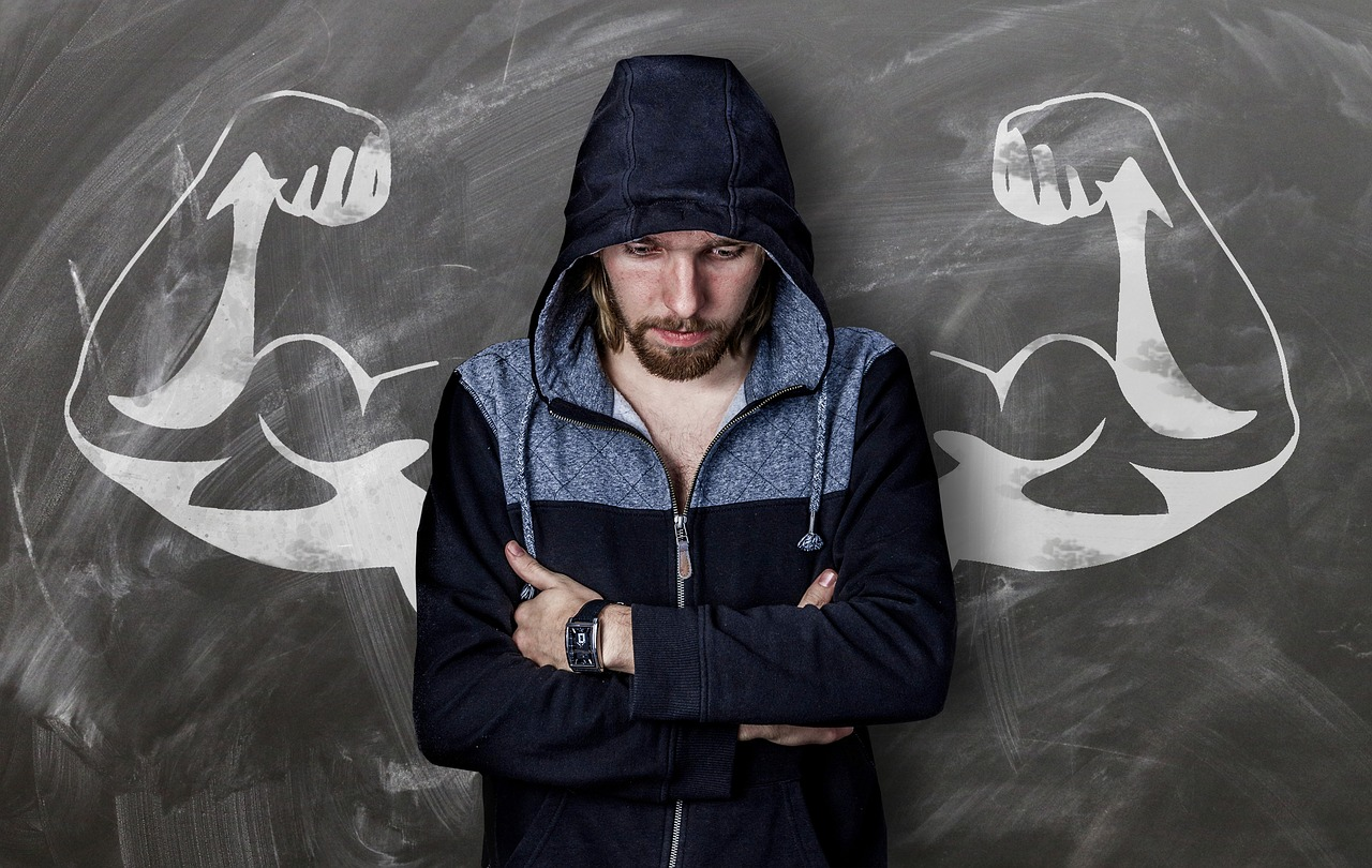 Man with arms folded in front of muscles drawn on blackboard
