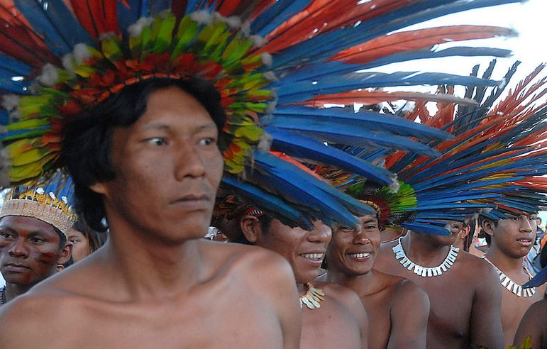 A line of men with feather headdress and some with necklaces.