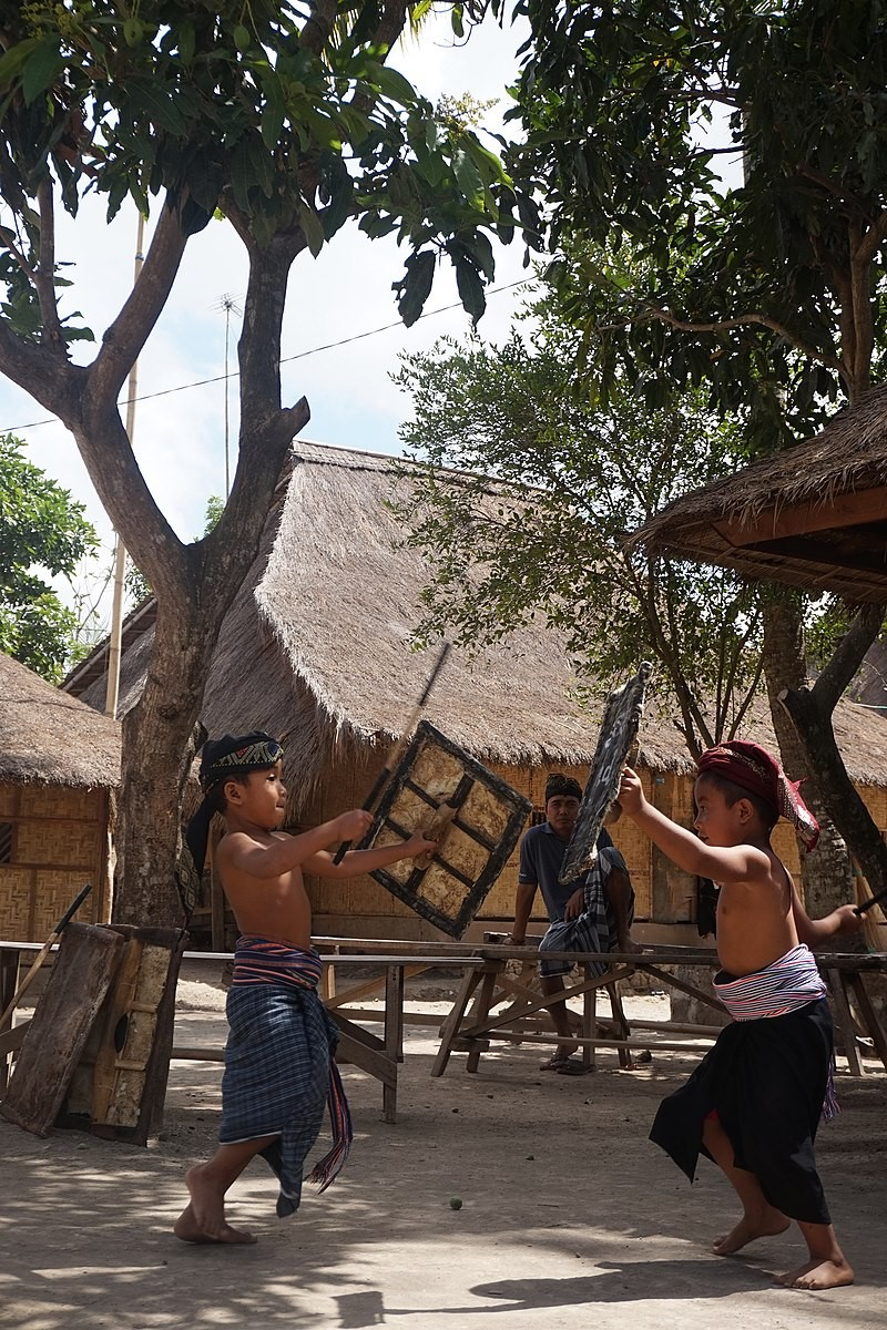 Two boys face each other with shields and sticks.