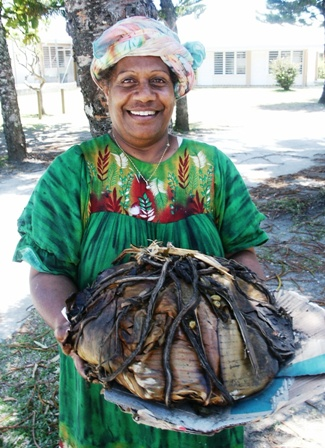 A Kanak woman holds a bundled dish in front of her.