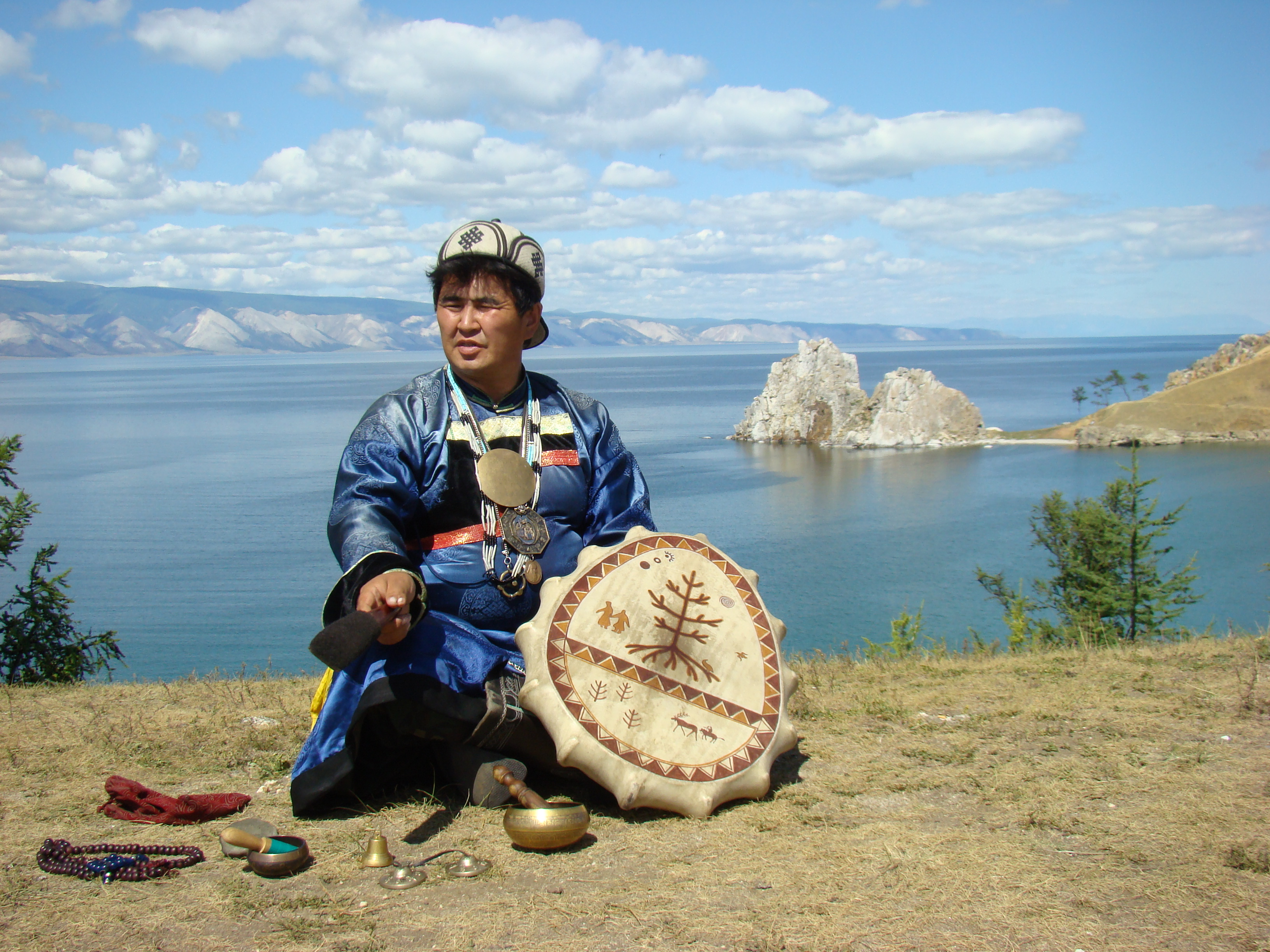 A ritually dressed shaman poses with his drum by the shore.