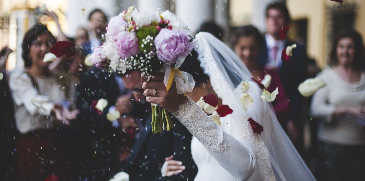 Bride holding flowers and rice thrown at wedding